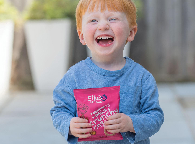 little boy holding Ella's Kitchen innovative packaging by Biles Hendry